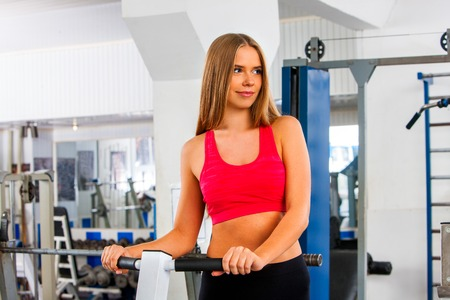 twisting: Fitness woman workout gym. Girl working on waist twisting disc. She looking away sport indoor. Stock Photo