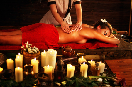 Massage of woman in spa salon. Girl on candles background treats problem back spa salon. Luxary interior with working masseuse in oriental therapy salon. Female bare back with smooth skin have relax . Stock Photo