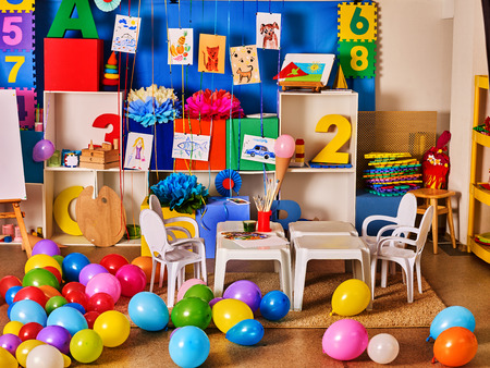 empty classroom: Kindergarten interior decoration child picture on wall. Preschool class waiting kids. Colour balloons on floor. Playroom with white table. Art room education childrens creativity. Mess in classroom.