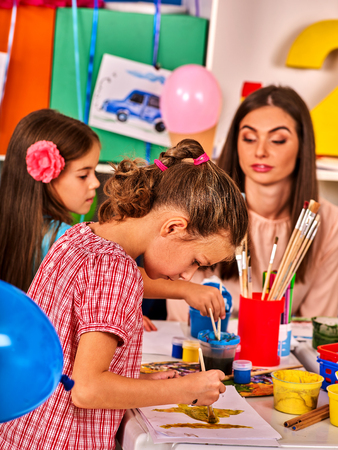 preschool children: Children painting and drawing in kids club. Craft lesson in primary school. Kindergarten teacher who smiling help small students. Group people work together. Balloons decoration room. Stock Photo