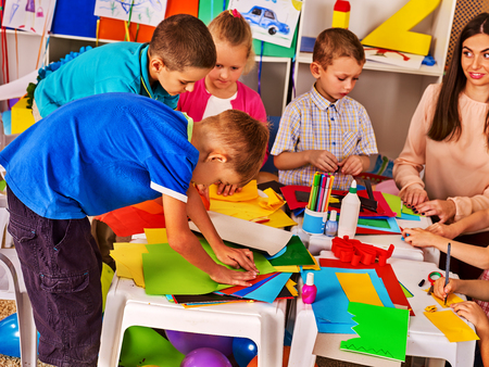Children cutting paper in class. Kids development and social lerning children in school. Childrens project in kindergarten. Low tables for work and creativity. Group girl , boy with teacher together. Archivio Fotografico
