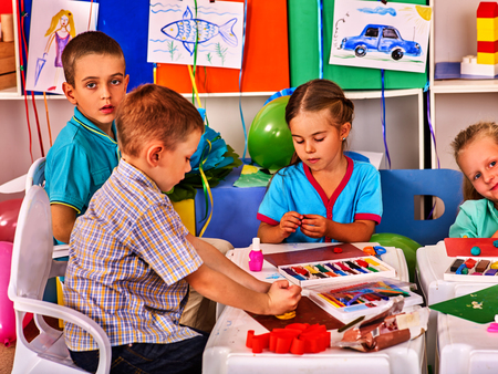 modeling clay: Child dough play in school. Plasticine for children. mold from plasticine in kindergarten .Kids knead modeling clay with hands in preschool. Childrens drawings on the walls of classrooms. Stock Photo