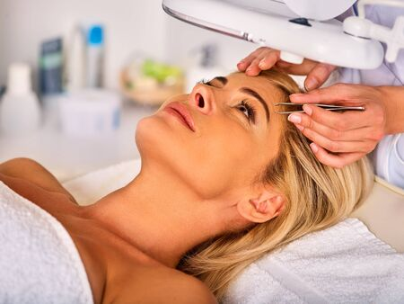 tweezing: Eyebrow treatment of woman middle-aged in spa salon. Tweezing eyebrow by beautician. 40s old female under cosmetic lamp. European facial procedure. Middle-aged patient looking up.