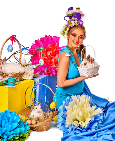 Easter girl holding bunny and eggs. Woman with holiday hairstyle and make up holding rabbit in basket with flowers. Adults at the festival. White background.