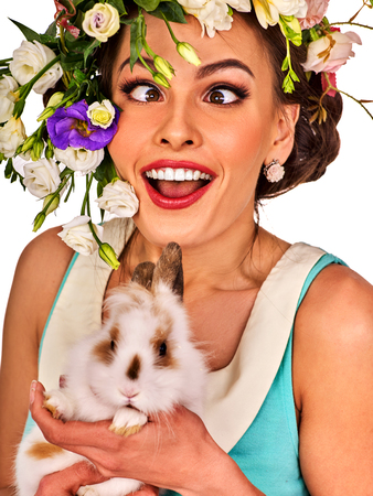 Easter girl holding bunny. Woman with holiday spring flowers hairstyle and make up with fake eyelashes. Adults at the festival. Female makes squint eye for fun. She has strabismus on white background. Banque d'images