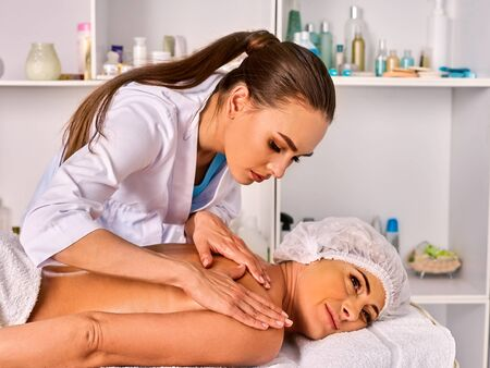 Massage therapy deals. Woman therapist making manual therapy back. Hands of masseuse close up. Treatment of spinal injuries 40 old client in spa salon. Young beautician on foreground. Masseuse use edge of palms.