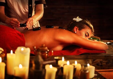relax massage: Hot stone massage rocks. Spa stones of woman in spa salon. Girl on candles background has therapy and skincare in luxary spa salon. Female bare back with smooth skin have relax .