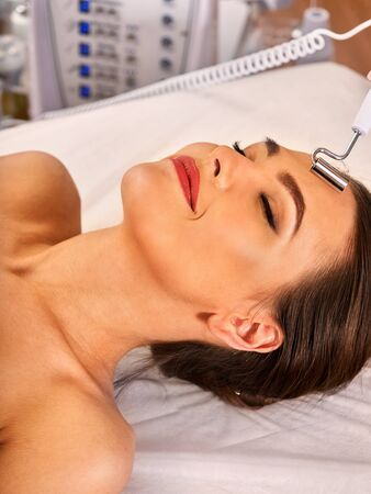 nu: Facial massage at beauty salon. Electric stimulation skin care of woman. Professional equipment for microcurrent lift face. Anti aging rejuvenation and non surgical treatment.