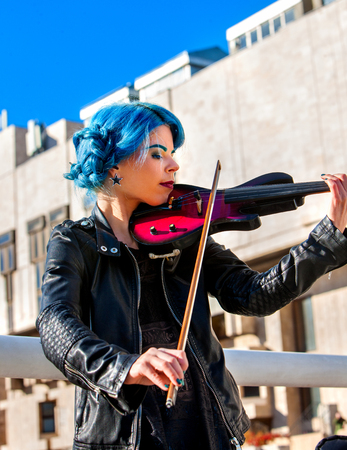 outdoor outside: Woman perform music on violin in park outdoor. Girl performing jazz on city street . Spring outside with blue hairstyle background.
