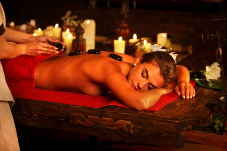 relax massage: Massage basalt hot stones of woman in spa salon. Girl on candles background has stone therapy and skincare in spa salon. Luxary interior in therapy. Female bare back with smooth skin have relax .
