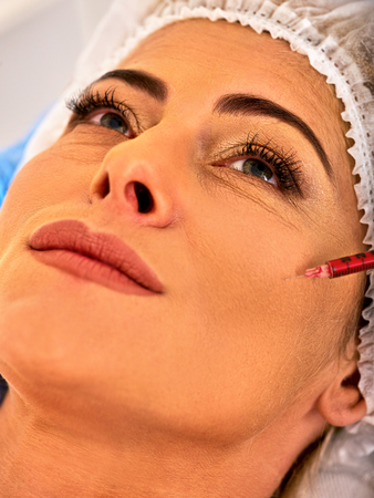 dermal: Dermal fillers of woman middle-aged in spa salon with beautician. Beauty woman giving  injections.