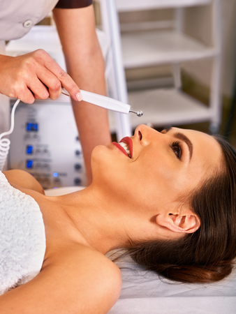 nu: Electronic facial lift massage at beauty salon. Electric stimulation skin care of woman. Professional equipment for face microcurrent therapy . Anti aging rejuvenation and non surgical treatment. Stock Photo