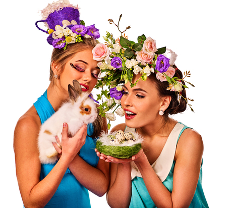 Easter girl together holding bunny. Women in holiday style celebrate take rabbits with and a basket with quail eggs. Adults at the festival. Isolated.