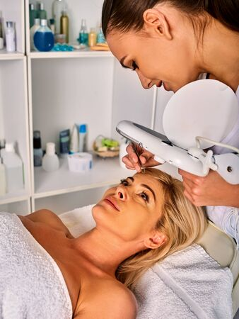 tweezing: Eyebrow treatment of woman middle-aged in spa salon. Tweezing eyebrow by beautician. 40s old female under cosmetic lamp. European facial procedure. Patient looking up. Medical room equipment.