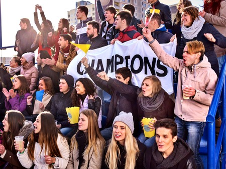 cheering fans: Fans cheering in stadium holding champion banner and singing on tribunes. Large group people together support your favorite team. People holding banner with Champion banner happily eating popcorn. Stock Photo