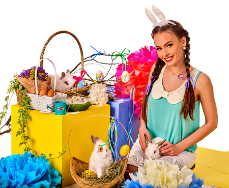 czech women: Easter bunny ears headband for women. Girl holding basket bunny and eggs. Woman with holiday hairstyle and make up touch rabbit with flowers. Adults at festival. White background isolated. Stock Photo