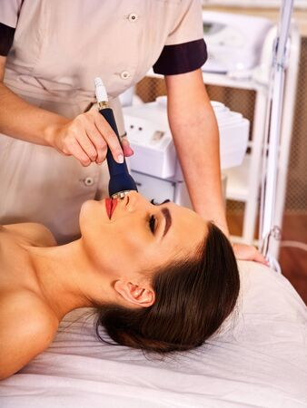 Ultrasonic facial treatment on ultrasound face machine. Woman with nude shoulders electric lift massage spa salon. Electronic stimulation female muscles. Professional equipment microcurrent therapy .