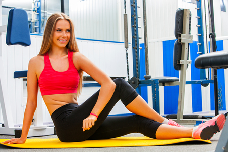 Stretching woman in sport gym. Twisting exercising for girl . Woman workout at fitness class. Twist for women. Middle section of bare back. Body that you want concept.