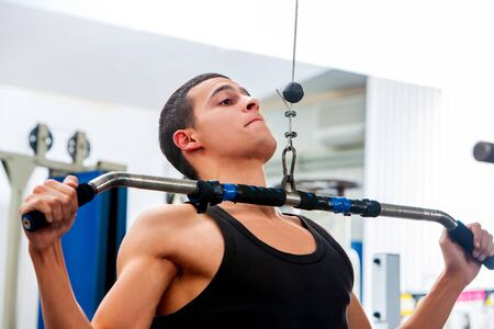 Man pulling on bar in gym. Top view of sportsman pull ups exercising in fitness center. Stock Photo
