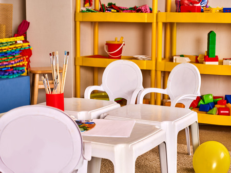 empty classroom: Kindergarten tables and chairs in interior decoration shelves for toys. Preschool class waiting kids. Colour balloons on floor. Playroom with white table. Art room for education childrens creativity. Stock Photo