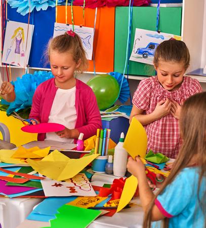 preschool children: Preschool scissors in kids hands cutting paper in class. Development and social lerning children in school. Childrens project in kindergarten. Small group girls with teacher together. Three people.