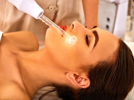 High frequency machine in spa salon. Young woman receiving electric darsonval facial massage after procedure at beauty room close up.