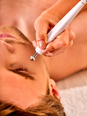 Man facial massage beauty salon. Electric stimulation man skin care . Professional equipment microcurrent lift face. Anti aging rejuvenation and non surgical treatment.