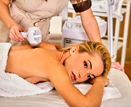 Ultrasonic body treatment on ultrasound skin care machine. Woman receiving electric lift massage at spa salon. Electronic stimulation female muscles. Professional equipment microcurrent therapy .