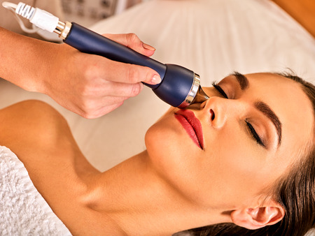 non: Ultrasonic facial treatment on ultrasound face machine. Woman with closed eyes has electric lift massage spa salon. Stimulation male muscles. Professional equipment microcurrent therapy in hand.