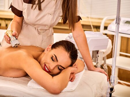 sound therapist: Woman back massage beauty salon. Electric stimulation female skin care . Professional equipment microcurrent body lift . Anti aging rejuvenation . Receiving electroporation beauty therapy indoor.