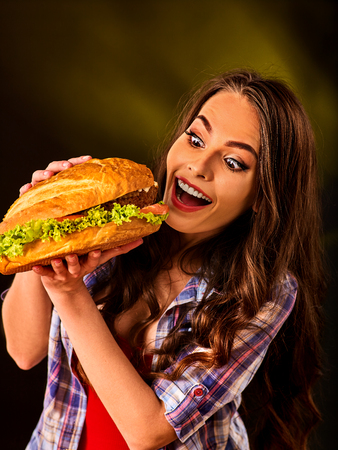 eating fast food: Woman eating hamburger. Student consume fast food. Girl bite of very big burger . Girl trying to eat a lot of junk. Advertise fast food on black background.