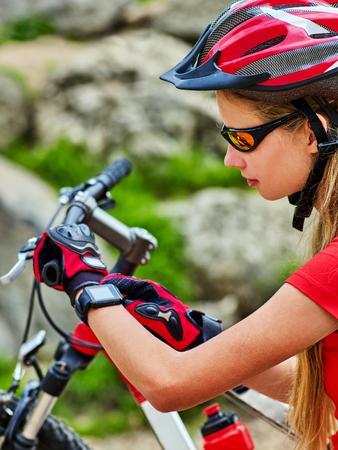 Woman traveling bicycle in summer park. Bicyclist girl watch on smart watches. Girl counts pulse after sport training and is looking for way to navigator. Cycling is good for health. Stock Photo