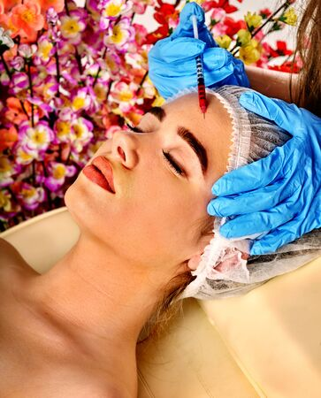 Filler injection for female forehead face. Plastic aesthetic facial surgery in beauty clinic. Beauty woman giving  injections. Doctor in medical gloves with syringe on spring flowers background. Stock Photo