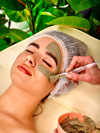 Mud facial mask of woman in spa salon. Massage with clay full face. Girl wearing medical hat on with therapy room. Female lying wooden spa bed. Beautician with brush therapeutic procedure green plant background. Stock Photo