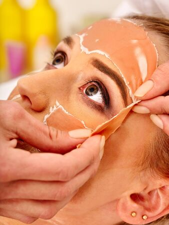 Collagen face mask . Facial skin treatment. Beautician removes mask from patient face close-up. Woman receiving cosmetic procedure in beauty salon.