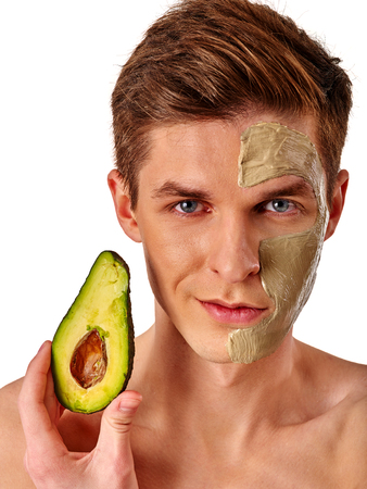 elasticidad: Facial mask from fresh fruits and clay for man concept. Face with treatment mud applied . Male holding avocado half for skin care procedure in salon.