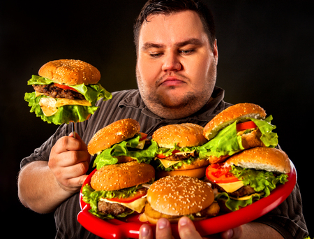 fast meal: Fat man eating fast food hamberger. Breakfast for overweight person. Junk meal leads to obesity. Person regularly overeats concept on black background.