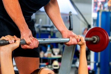 Fitness friends workout gym. Woman working on bench press. Cropped shot of she lifting barbell. Trainer backs girl while taking exercises.