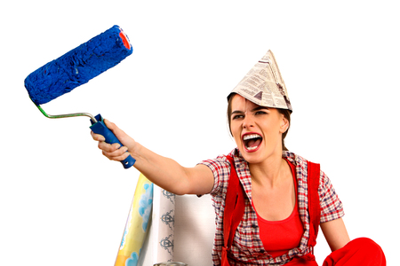 dwelling: Repair home woman holding paint roller for wallpaper. Aggressive screaming girl in newspaper cap renovation apartment on isolated. Stock Photo