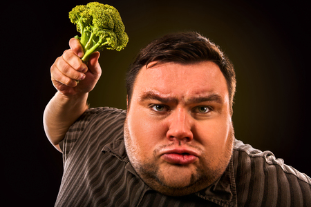 no person: Diet fat man eating healthy food . Health breakfast with vegetables broccoli for overweight person. Male trying to lose weight but he can no longer eat cabbage.