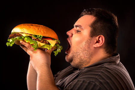 Diet failure of fat man eating fast food hamberger. Breakfast for overweight person who spoiled healthy food by eating huge hamburger. Junk meal leads to obesity. Person regularly overeats concept . Stockfoto