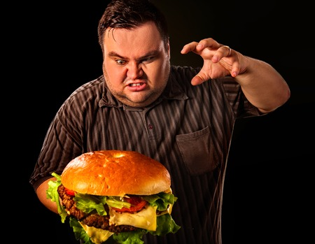 fast meal: Diet failure of fat man eating fast food hamberger. Aggressive overweight person who spoiled healthy food by eating huge hamburger. Junk meal leads to obesity. Stock Photo