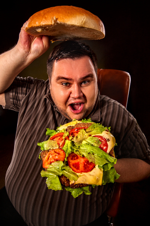 junk food: Diet failure of fat man eating fast food hamberger. Humor breakfast for overweight person who spoiled healthy food by eating huge hamburger. Junk meal leads to obesity. Bun size of concept. Stock Photo