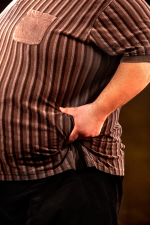 crease: Man belly fat man holds to crease of fat on his stomach black background. Cropped shot of male body.