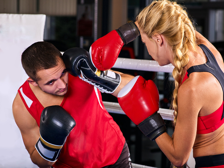 Boxing workout woman in fitness class ring. Sport box exercise two people. Man trainer holding sport mitts in gym. Female box gloves are red backview.