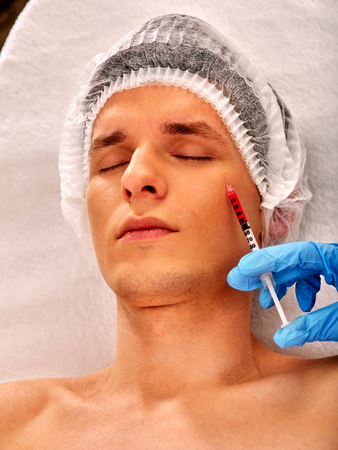 dermal: Filler injection for male face. Plastic aesthetic facial surgery in beauty clinic. Man giving anti-aging injections for pull up face contour . Doctor hand in medical gloves with syringe injects drug. Stock Photo