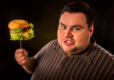 fast meal: Diet failure of fat man eating fast food hamberger. Aggressive overweight person who spoiled healthy food by eating huge hamburger on fork. Junk meal leads to obesity.