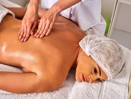 Massage room for therapy deals. Elderly woman therapist making manual therapy back. Hands of masseuse treatment of spinal injuries 40 old mature client in spa salon. Top view of lady in medical hat.