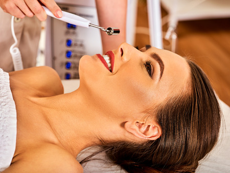 specials: Facial massage at beauty salon. Electric stimulation skin care of woman. Professional equipment for microcurrent lift face. Anti aging neck non surgical treatment. Electrical appliance close-up.