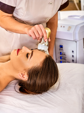 resurfacing: Skin resurfacing facial procedure on gold ultrasound face machine. Female acne treatment. Woman receiving electric lift massage at spa salon. Electronic stimulation female muscles. Indoor.